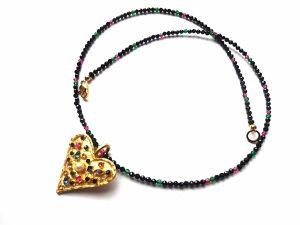 Špinelio vėrinukas su rubinais ir smaragdais ir auksuota širdele su įvairiaspalviais cirkoniais