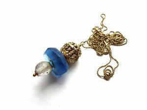 Prabangus mėlyno stiklo ir ažūrinės žalvarinės detalės pakabutis